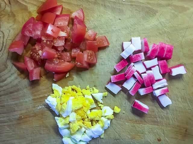 Нарезаем помидоры, яйца и крабовые палочки