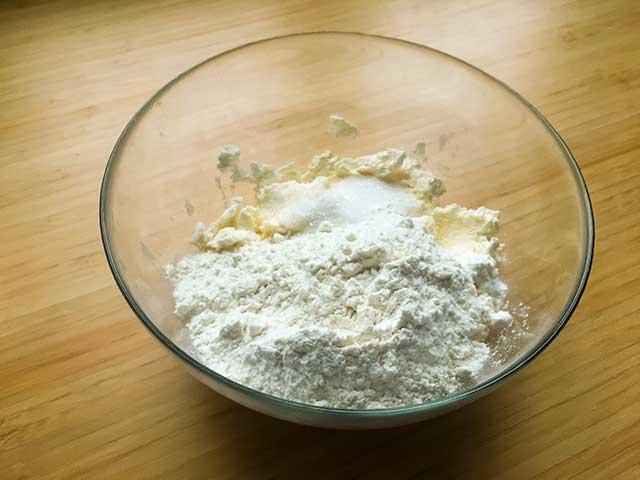 Мука, сахар, творог и маргарин в чашке